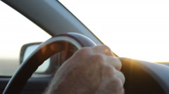 Close Up of hands on the steering wheel while driving during sunset - stock footage