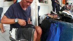 Shoe repair job at sidewalk Stock Footage