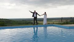 Wedding Couple Walks Edge Pool View - 4k - Slow Motion Stock Footage