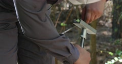 Man Fixes His Hand Brace Device Used For Drilling and Taking Land Samples For Stock Footage