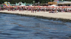 Dirty beach full of debris and algae which do not want to swim. Stock Footage