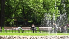 People spend freetime in park with burble fountain water . 4K Stock Footage