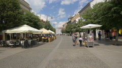 People relaxing at an outdoor restaurant on Nicolae Balcescu Street, Sibiu Stock Footage
