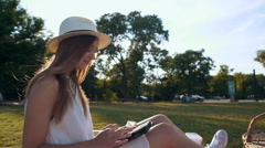 Pretty young girl with hat using tablet computer  on picnic - stock footage