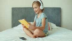 Girl listening music in headphones and reading book. Child resting Stock Footage