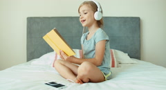 Girl listening music in headphones and reading hugging book Stock Footage