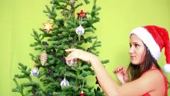 Beautiful teenager girl in Winter Hat decorating the Christmas tree on a green Stock Footage