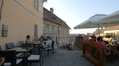 Tourists resting outside Atrium Cafe and children playing, Sibiu Stock Footage