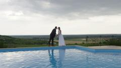 Wedding Couple Pool Edge Kiss Holding Hands  -  4k - Slow Motion Stock Footage