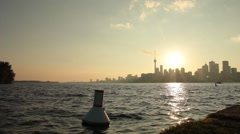 Buoy bobbing of lake ontario pier with skyline in the background Stock Footage