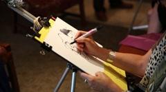 A cartoonist drawing cartoon portrait using a sharpie Stock Footage