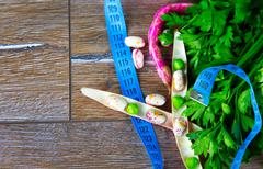 Stock Photo of Parsley and Beans and Measurement on Wooden Ground