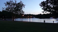People running and walking around a lake in the evening. Stock Footage