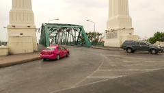 Different vehicles drive to and from steel bridge, passing between stelas Stock Footage