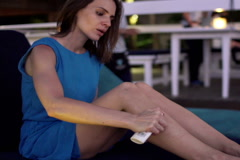 Woman applying relief spray on mosquito bite sitting in deckchair in cafe  NTSC Stock Footage
