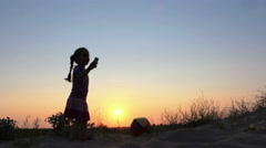 Silhouette of a dancing little girl against the sunset, Slow Motion Stock Footage