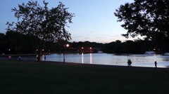 People running and walking around a lake in the evening. - stock footage