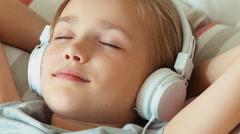 Extreme closeup portrait girl child listening music in headphones with eyes Stock Footage