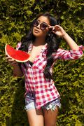 Beautiful asian girl in sunglasses with watermelon poses  front of green bush Stock Photos