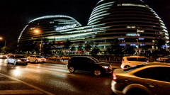 Walking along the street, night view of Galaxy SOHO shopping mall in Beijing. Stock Footage