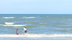 Pretty woman in white T shirt walking with the boy red T shirt on beach Stock Footage