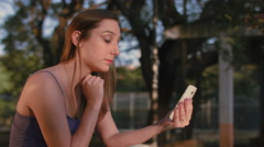 A woman using your smartphone in a park Stock Footage