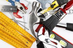 Assortment of tools on plain background - stock photo