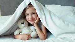 Girl hugging teddy bear under the blanket and smiling at camera Stock Footage