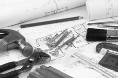 Assorted work tools on building plans - stock photo