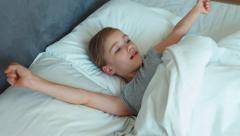 Girl wakes up and stretching in a bed and smiling Stock Footage