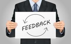 businessman holding feedback poster - stock illustration