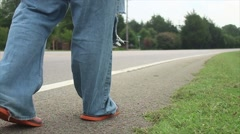 Man Walks Down Side Of The Road In Tattered Jeans - stock footage
