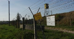 Grim Looking Barbed Wired Fence and a Guard Tower With a Yellow Prohibition Stock Footage