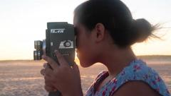Girl Filming With Vintage Film Camera on Beach Stock Video Stock Footage