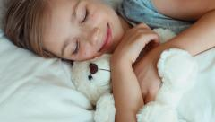 Portrait girl child hugging teddy bear in a bed. Top view Stock Footage