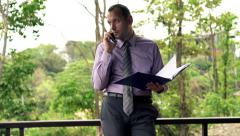 Young businessman with documents talking on cellphone standing on terrace Stock Footage