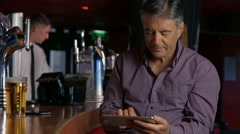 Stock Video Footage of Man having a pint at  the bar using tablet