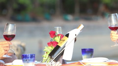 Woman and man touch  glasses at table served at beach Stock Footage