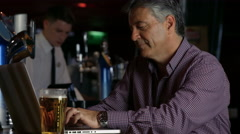 Stock Video Footage of Man having a pint at  the bar using laptop