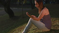 A beautiful woman sitting in a park slide some photos in your tablet Stock Footage