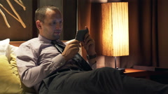 Young businessman watching movie on smartphone lying on bed at night Stock Footage