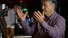 Stock Video Footage of Frustrated man having a pint at  the bar using laptop