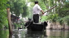 Fisherman training fish hawk on canal Stock Footage