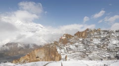 TIMELAPSE village in snow on cliff with clouds,Dankhar,Spiti,India Stock Footage