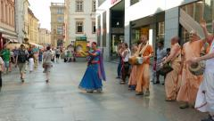People from the Hare Krishna movement dancing and singing on the street Stock Footage