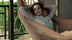 Happy, young businesswoman relaxing while lying on hammock Stock Footage