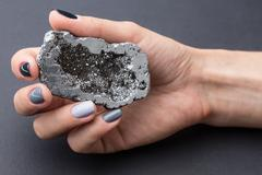 Female hand with textured silver mineral - stock photo