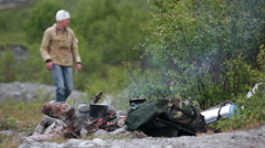 Bonfire in the camp in mountains and mature man hiker searching firewoods Stock Footage
