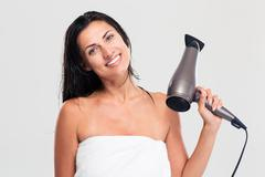 Woman in towel holding hairdryer - stock photo