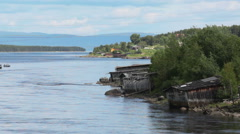 Old wooden boat barns on the Kovda river, north of Murmansk District, Russia Stock Footage
